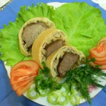 Мясо в тесте на салатных листьях с помидорами
