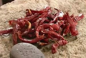 Красные стручковые перцы на камне