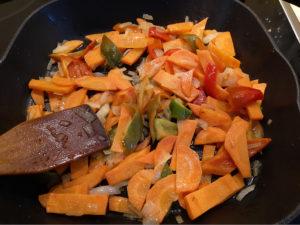 Слегка обжаренные лук, морковь и болгарский перец на сковороде