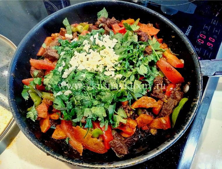 Добавляем кинзу и чеснок к мясу в сковороду для аромата