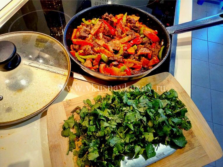 Режем кинзу для добавления в мясо в сковороду для аромата
