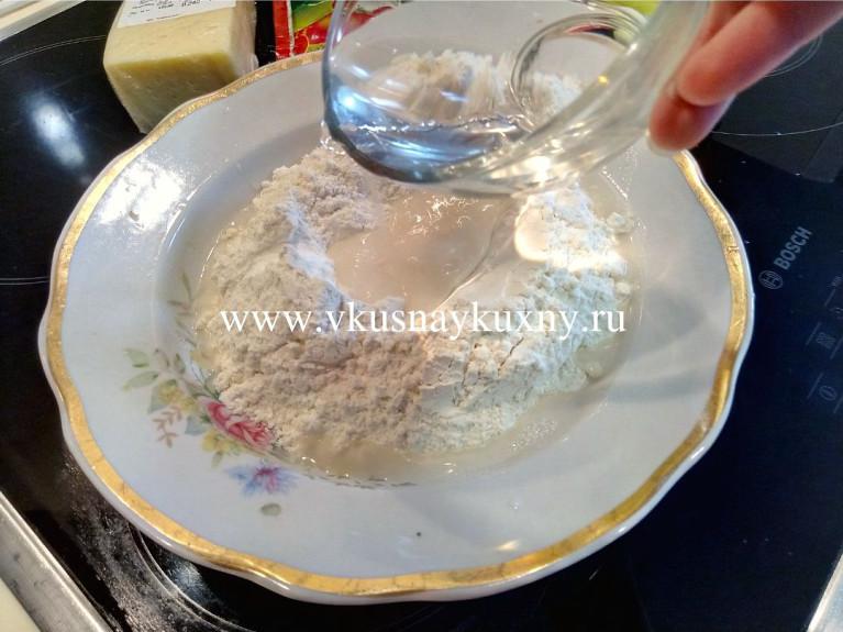 Вливаем воду в муку с солью и замешиваем тесто