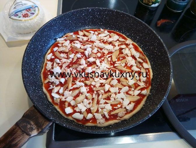 Раскладываем кусочки сыра поверх томатного соуса для пиццы равномерно