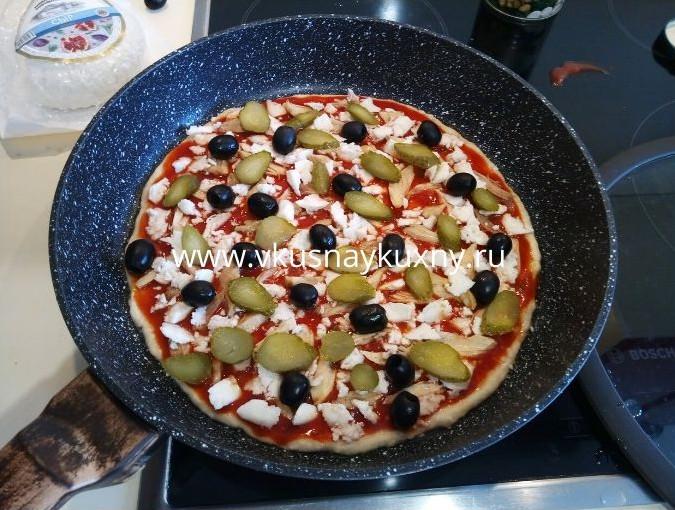 Раскладываем маслины и корнюшоны поверх томатного соуса для пиццы равномерно