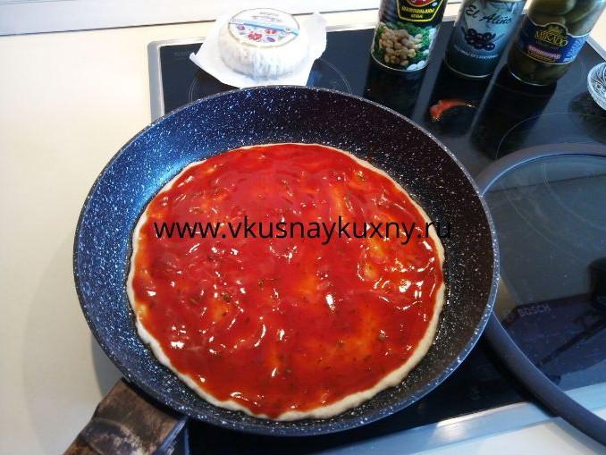 Смазанное тесто для пиццы томатным соусом ровным слоем