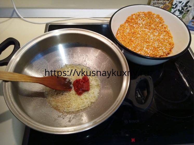 Добавляем томатную пасту в обжаренный лук в кастрюле ВОК