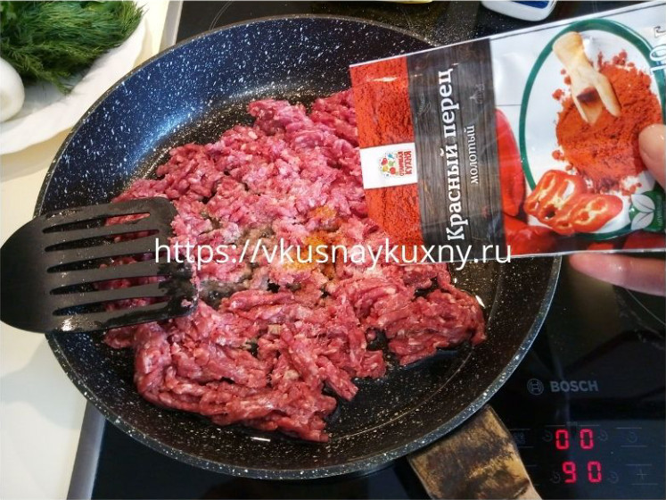 Перчим красным острым перцем фарш на сковороде и обжариваем